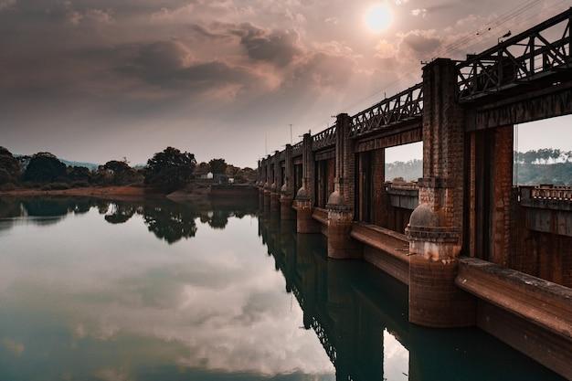 Bella vista su un vecchio ponte di pietra che si riflette nell'acqua limpida del fiume all'alba