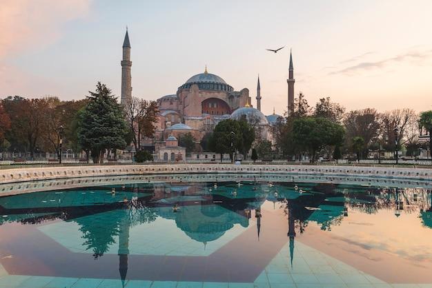Прекрасный вид на собор святой софии в стамбуле, турция с отражением в фонтане на восходе солнца с никем. пункт назначения