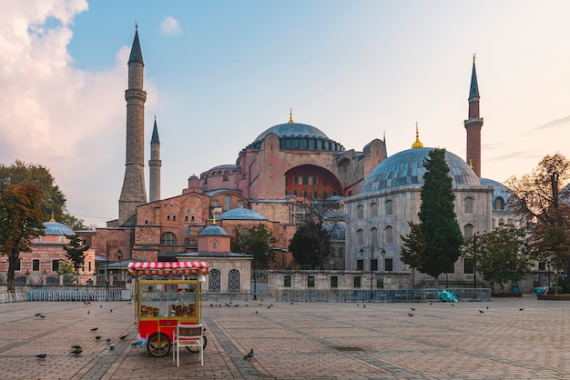 Прекрасный вид на собор святой софии в стамбуле, турция с simit тележкой на пустой площади на восходе солнца. пункт назначения