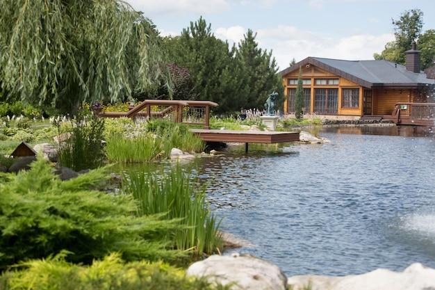 Прекрасный вид на озеро с деревянным пирсом и домом в солнечный день