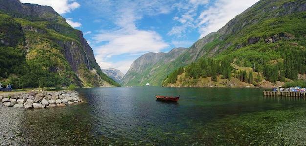 푸른 하늘 배경에 노르웨이 바다 운하 물에 보트와 산에 녹색 숲과 자연의 아름다운 전망