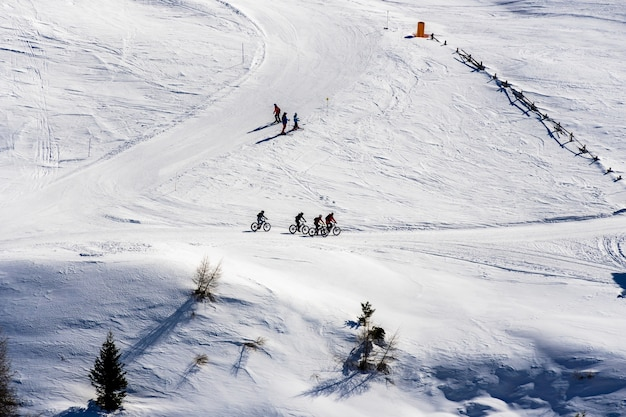 Beautiful view of people cycling and skiing across snowy mountains in south tyrol, dolomites, italy