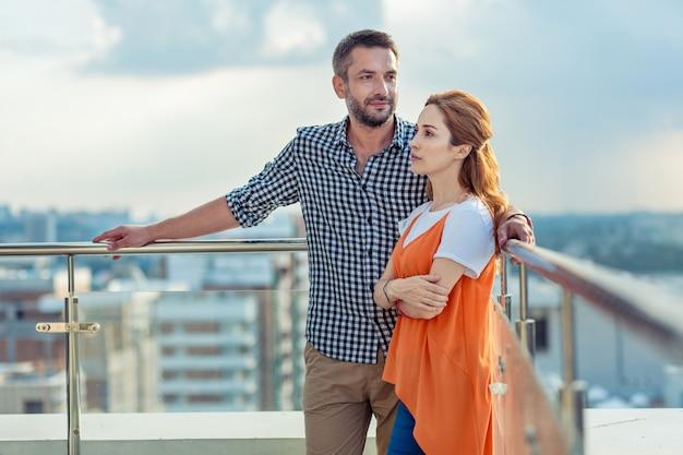 美しい景色。建物の上にいる間一緒に立っている楽しい素敵なカップル