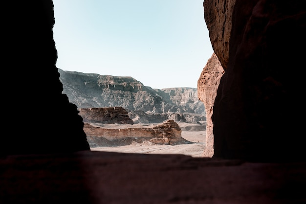 Beautiful view of the rocks and cliff in a desert captured from inside a cave
