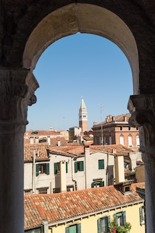 Beautiful view of san marco tower through an ancient arch. venezia