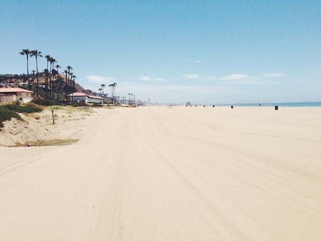 Bella vista sulla spiaggia di sabbia con edifici e montagne vicino alla riva