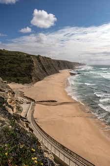Beautiful view of sandy beach with a pathway on the cliff