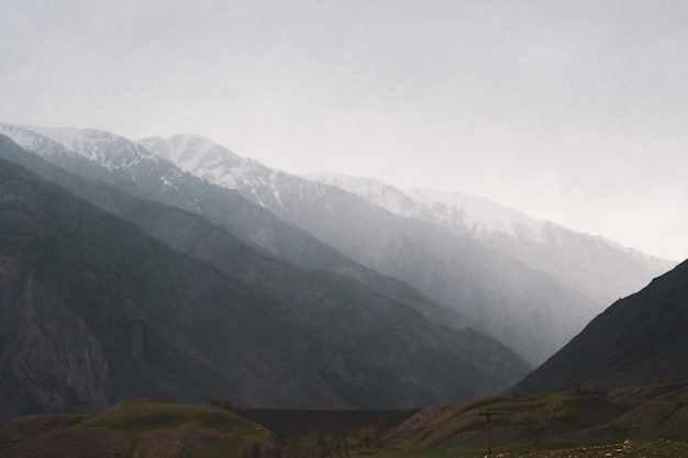 Beautiful view of the silhouettes of the altai mountain ranges in rainy weather and fog