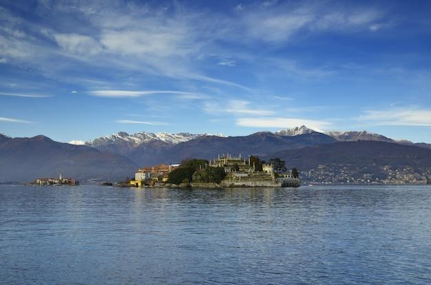 Bella vista di una piccola isola in mezzo al mare vicino alle montagne sotto il cielo blu