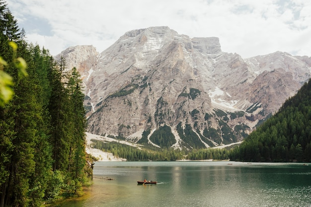 Beautiful view of traditional wooden rowing boat on scenic lago di braies in the dolomites, south tyrol, italy.