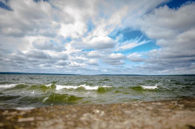 Bella vista sul mare ondoso sotto il cielo nuvoloso