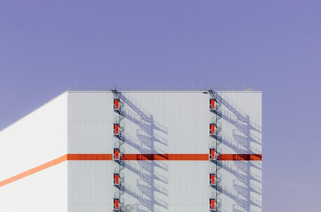 Beautiful view of a white building with an orange line across it and a staircase to the roof