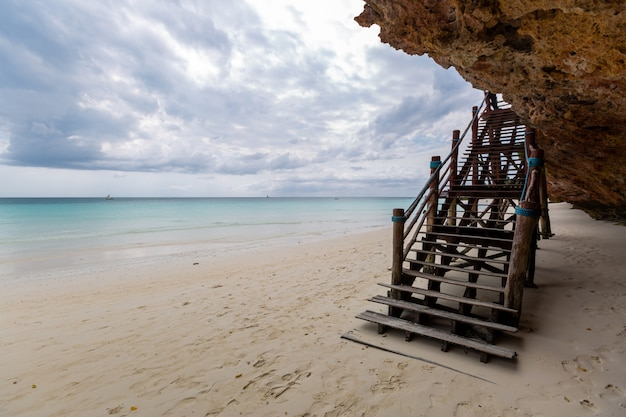 La bella vista di una scala di legno sulla spiaggia dall'oceano ha catturato a zanzibar, africa