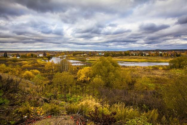 秋のロシアの美しい村、曇り空の下で美しい黄色の木々