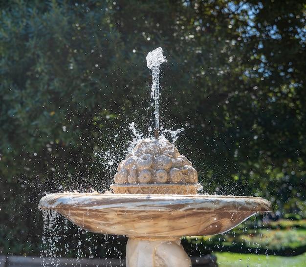 Красивый старинный фонтан в саду
