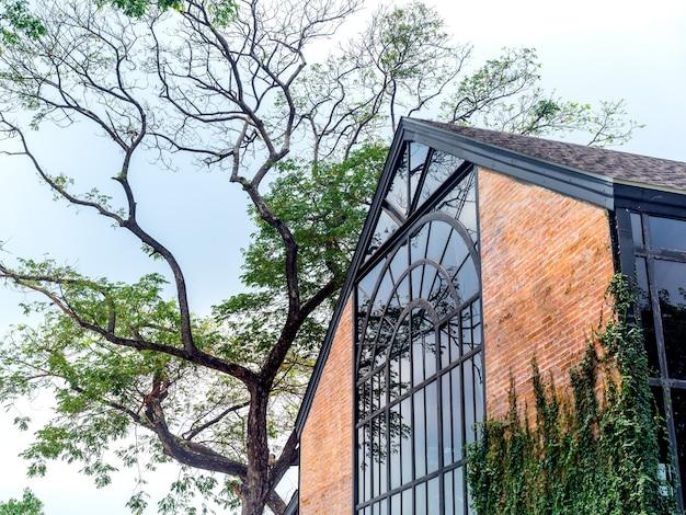Красивое винтажное стеклянное жилищное строительство с экстерьером кирпичной стены на голубом небе.