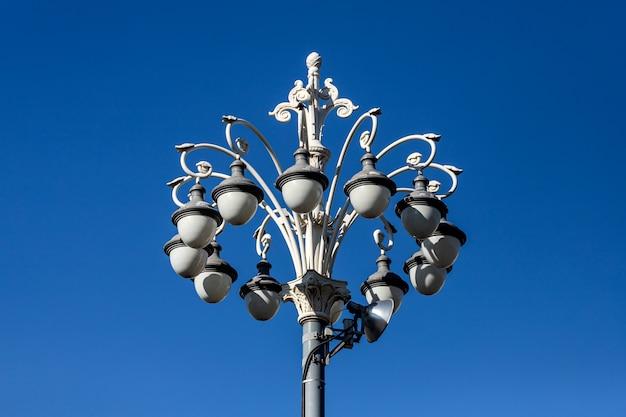 소용돌이와 하늘을 배경으로 곱슬거리는 아름다운 빈티지 램프 포스트. 거리와 공원의 장식. 도시와 마을의 거리 조명