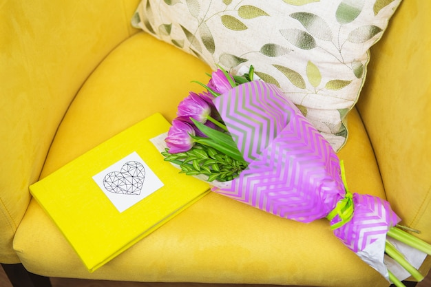 Beautiful violet bouquet of tulips on a yellow stool and yellow book