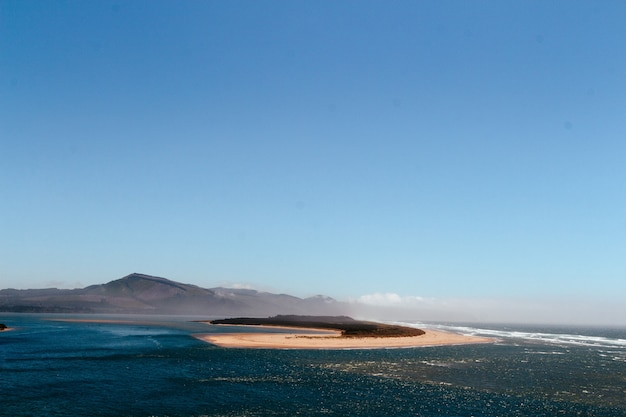 Beautiful vista of the sea with a little sandy island in the middle and hills