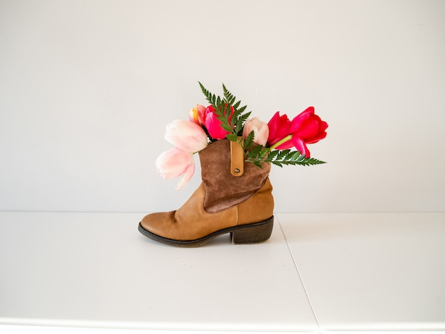 Beautiful vivid tulips with green fern in brown female leather boot on white background