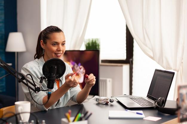 최신 장비를 사용하여 소셜 미디어에서 라이브 메이크업 튜토리얼 공유를 만드는 아름다운 블로거. 인플루언서 블로거 책상에 앉아 뷰티 커뮤니티를 위한 조언을 공유하는 비디오 블로그 녹화
