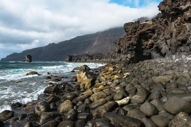 岩と溶岩層のある美しい火山の海岸線の風景。