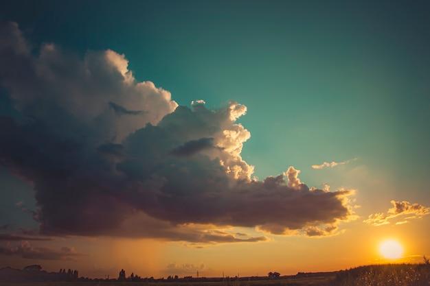 夕日とフィールドの地平線と青空の美しいボリュームクラウド