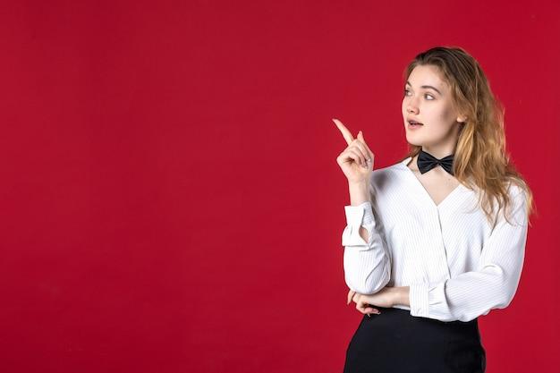 Bella cameriera donna farfalla sul collo e puntando qualcosa sul lato destro su sfondo rosso