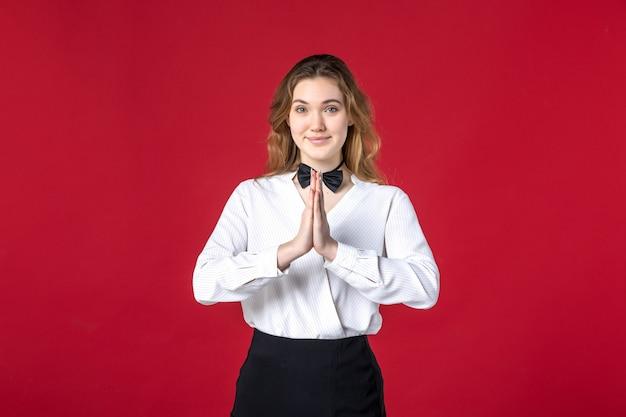 赤い背景に感謝のジェスチャーを作る美しいウェイトレスの女性