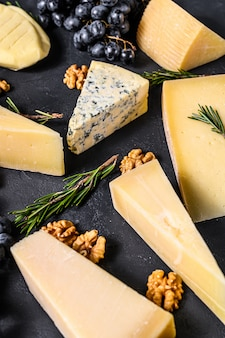 Красивая стена с различными видами вкусного сыра, грецких орехов и винограда. вид сверху
