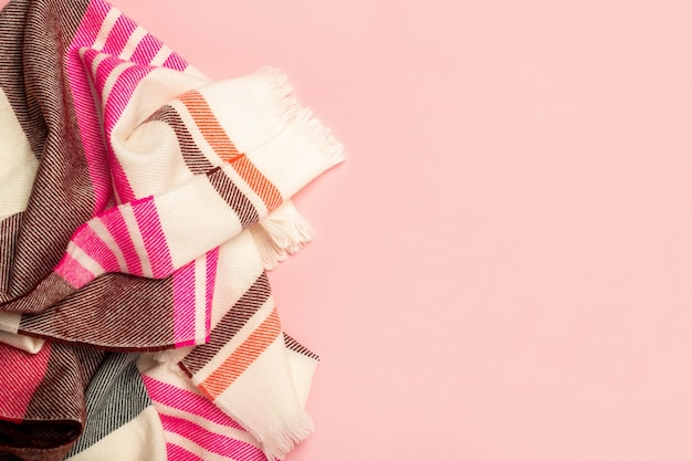 Beautiful warm scarf on a pink background. natural woolen fabric, fragment of a sweater for design. banner. flat lay, top view.