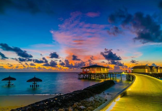 일몰 시간에 열대 몰디브 섬의 아름다운 워터 빌라