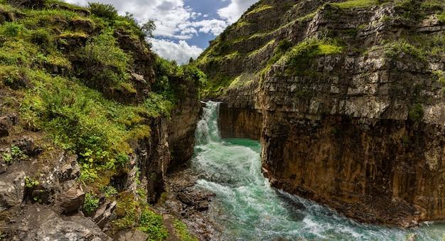 緑の岩の間の美しい滝