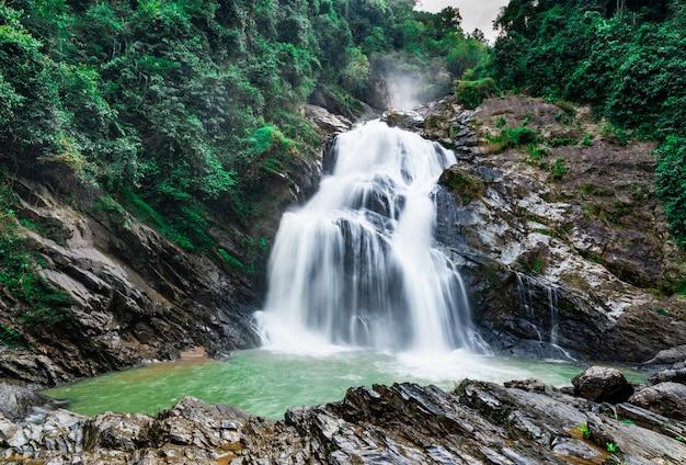 青い空と白い積雲の雲と山の美しい滝。熱帯の緑の木の森の滝。ジャングルの中を滝が流れています。