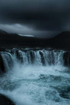 A beautiful waterfall in a field with dark sky