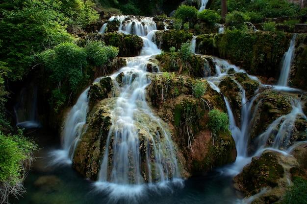 Красивый водопад, протекающий через пышный зеленый лес