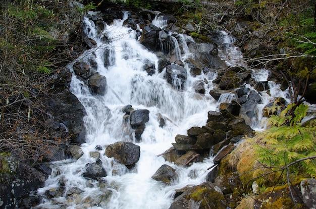 岩に囲まれた小川に流れ落ちる美しい滝