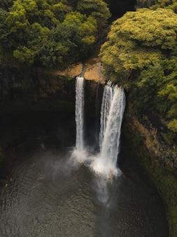Красивый водопад, впадающий в реку в окружении зелени
