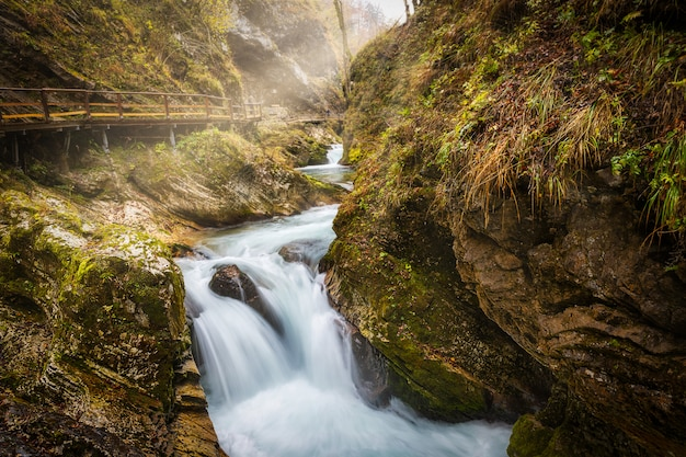 Beautiful waterfall and wooden pathway in vintgar gorge with morning sunlight, famous touristic destination in slovenia