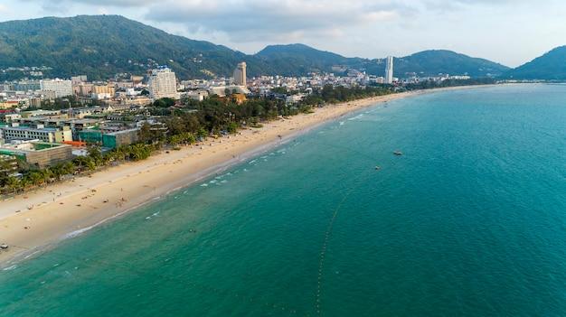 Beautiful wave crashing on sandy shore at patong beach in phuket thailand, aerial view