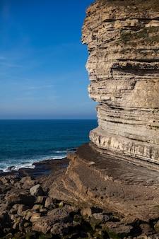 흐린 하늘 아래 바위 절벽을 때리는 아름다운 물결 모양의 바다