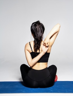 The beautiful wearing exercise suit,sitty on mat,show backside,raise hands cross her body ,posing basic yoga pattern,at studio