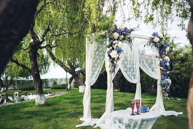 自然の中で美しい結婚式のアーチとテーブル。結婚式の装飾。