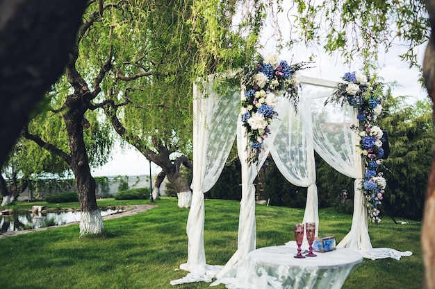 Beautiful wedding arch and table in the nature. wedding decorations.