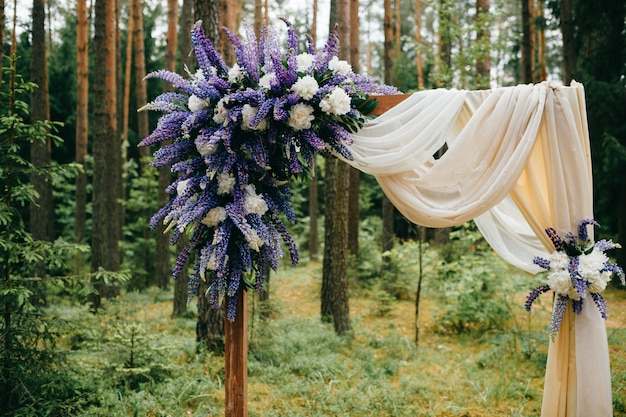 Beautiful wedding arch with blue flowers and decorative elements standing in forest. wedding scenery in rustic style
