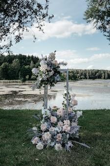 아름다운 결혼식 아치 밑의 통로. 복숭아와 은빛 천과 꽃으로 장식된 아치.