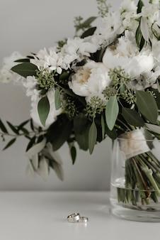 아름다운 웨딩 부케와 세련된 반지가 회색에 놓여 있습니다.
