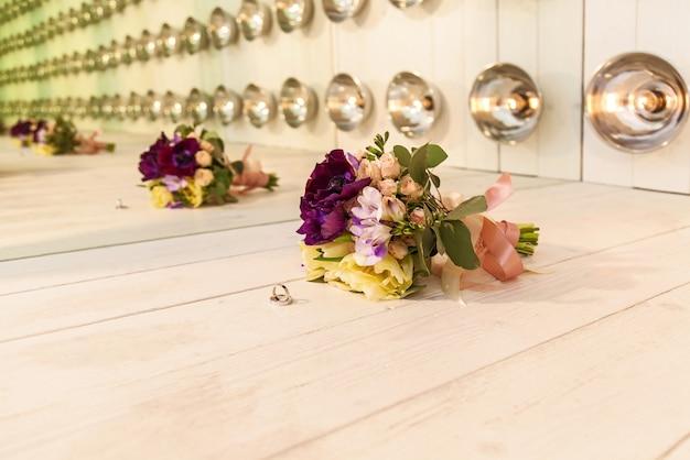 ランプを背景にした珍しいインテリアの美しいウェディングブーケと結婚指輪