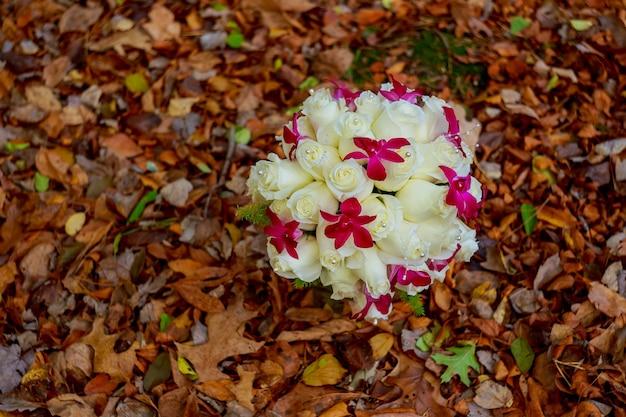 잎의 배경에 흰 장미의 아름다운 웨딩 부케 신부 부케