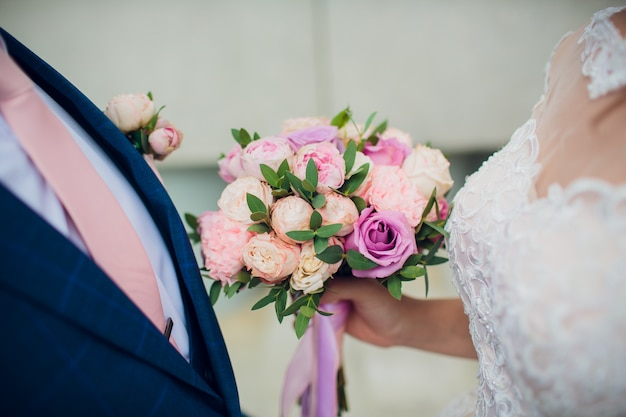 Beautiful wedding bouquet in bride's hands. hydrangea, eustoma, roses in bride's bouquet.